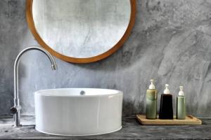 Vasque de salle de bain avec miroir en bois au dessus et pots à savon à côté