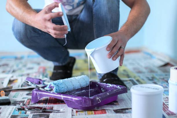 Homme accroupi en train de verser un pot de peinture blanche dans un bac