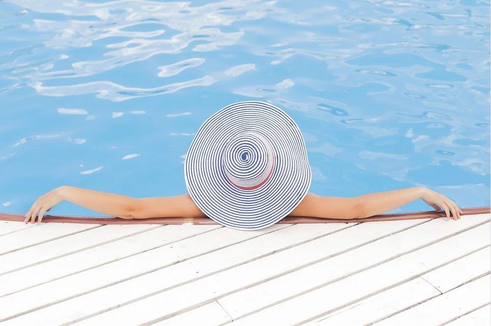 Jeune femme qui se fait bronzer au bord de sa piscine